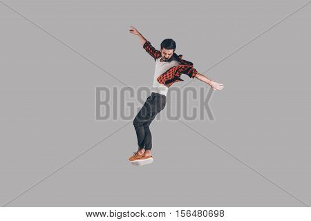 Feeling freedom in every move. Mid-air shot of handsome young man jumping and gesturing against background