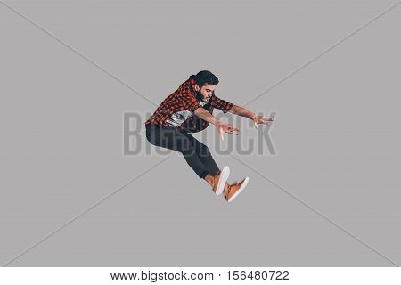 Jump in motion. Mid-air shot of handsome young man jumping and gesturing against background