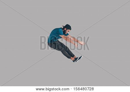 Enjoying freedom in every move. Mid-air shot of handsome young man in cap jumping and gesturing against background