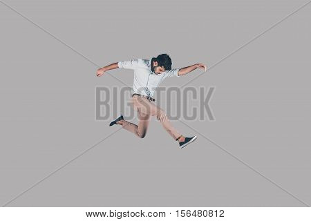 Man jumping. Mid-air shot of handsome young man jumping and gesturing against background