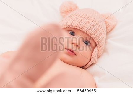 adorable 5 months old baby girl wearing knitted hat and hold her feet up and looks at the camera