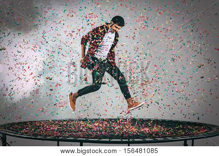 Mid-air fun. Mid-air shot of handsome young man jumping on trampoline with confetti all around him