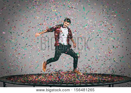 Trampoline and confetti. Mid-air shot of handsome young man jumping on trampoline with confetti all around him