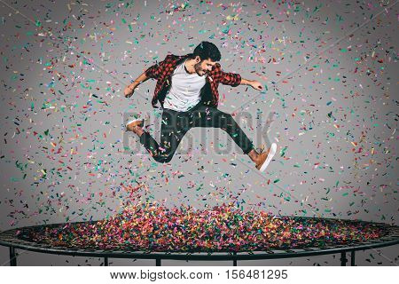 Living a bright life. Mid-air shot of handsome young man jumping on trampoline with confetti all around him