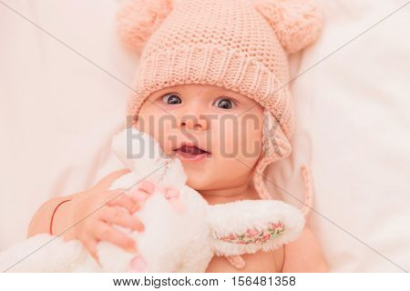 close up picture of an adorable baby girl hugging her toy bunny