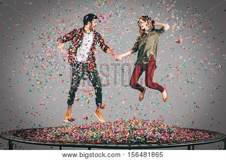 Carefree fun. Mid-air shot of beautiful young cheerful couple holding hands while jumping on trampoline together with confetti all around them