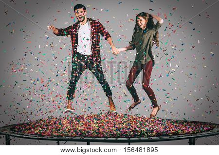 Just for fun. Mid-air shot of beautiful young cheerful couple holding hands while jumping on trampoline together with confetti all around them