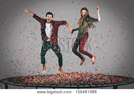 Fun in motion. Mid-air shot of beautiful young cheerful couple holding hands while jumping on trampoline together with confetti all around them