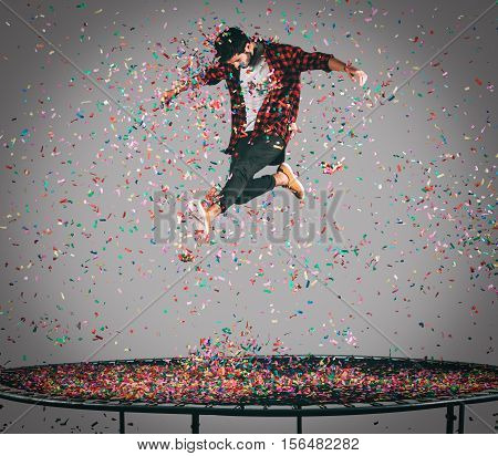 Carefree fun. Mid-air shot of handsome young man jumping on trampoline with confetti all around him