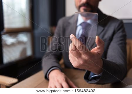Technological advances. Selective focus of a sophisticated modern smartphone being in hands of a confident successful handsome businessman