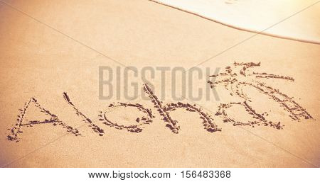 Aloha written text with palm tree on sand at beach
