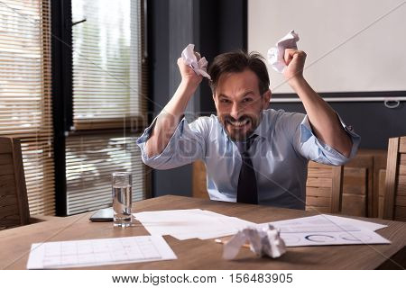 Stress at the workplace. Angry furious hysterical man crumpling paper and grimacing while being at work