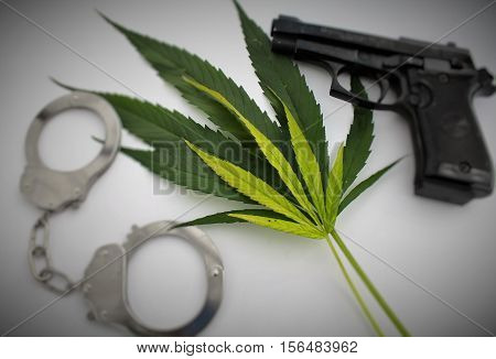 Marijuana cannabis leaves and handciffs and gun