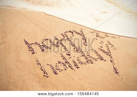Happy holiday written text on sand at beach