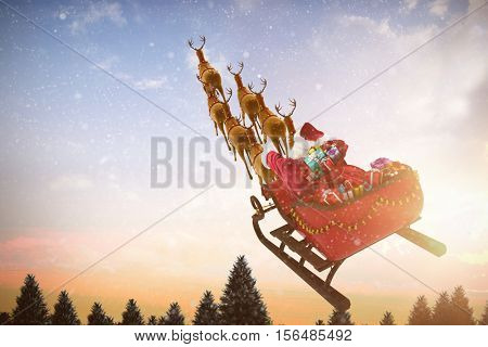 High angle view of Santa Claus riding on sled with gift box against snow falling on fir tree forest