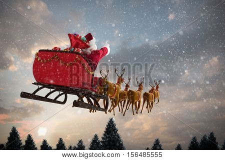 Santa Claus riding on sleigh with gift box against snow falling on fir tree forest