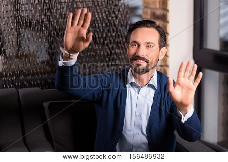 Absolutely transparent. Happy bearded handsome man pressing his palms to the virtual screen and smiling while sitting on the couch