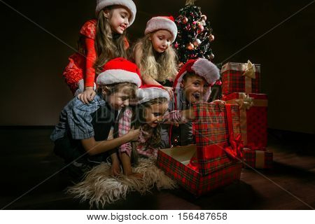 Group of children in Christmas hats open gift