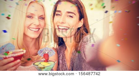 Beautiful women taking selfie with mobile phone against flying colours
