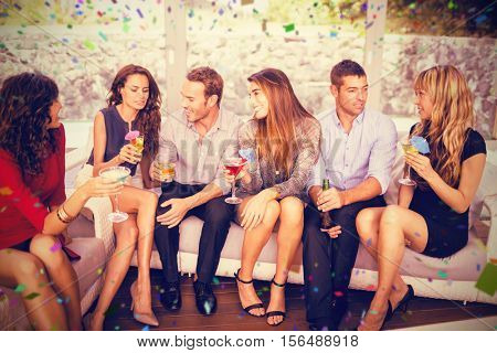 Group of friends talking and having drinks against flying colours