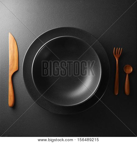 plate and cutlery on a black table