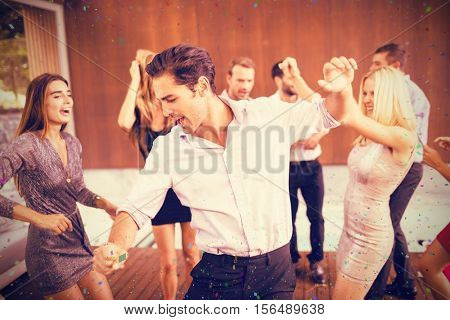 Cheerful friends dancing in party against flying colours