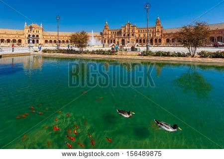 Spain Square or Plaza de Espana in Seville in the sunny summer day, Andalusia, Spain. Goldfish and ducks in the channel in the foreground