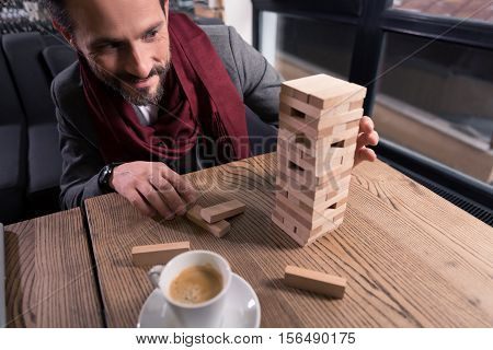 Board games. Joyful nice amused man playing jenga and having fun while relaxing after work