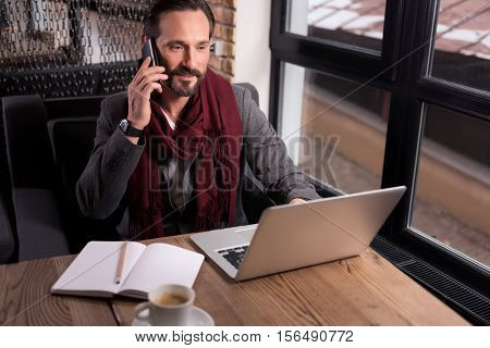 Discussing business issues. Handsome joyful confident businessman sitting in front of the laptop and having a phone conversation while working
