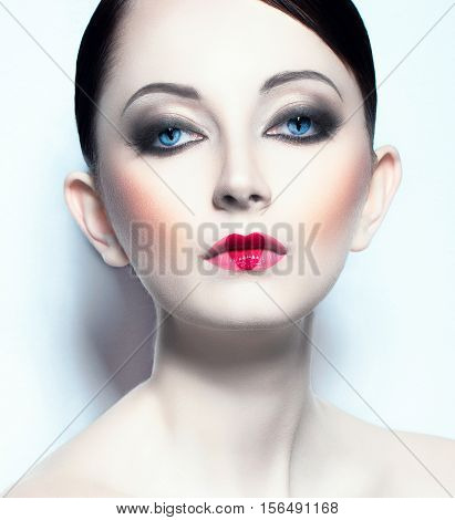 Portrait of a beautiful young woman like doll with a glamorous cool makeup