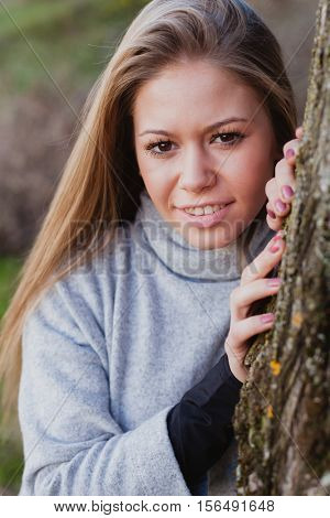 Beautiful woman behide to athe trunk of a tree on a day in autumn