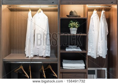 Modern interior wardrobe with shirt pants hat and towel in shelf.