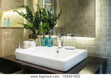 Interior of bathroom with sink basin faucet and white towel. Modern design of bathroom.