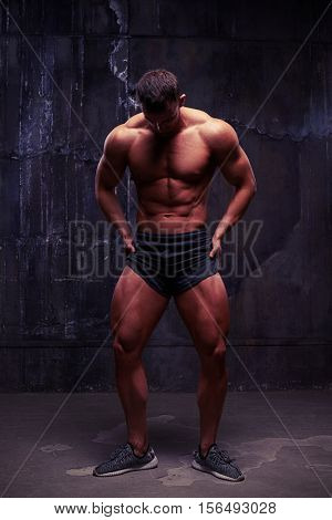 Studio photoshooting of young handsome bodybuilder, short upper lightning emphasizing the perfect relief of his well-trained sexy body