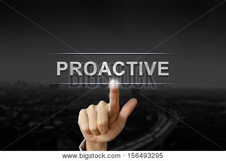 business hand clicking proactive button on black blurred background