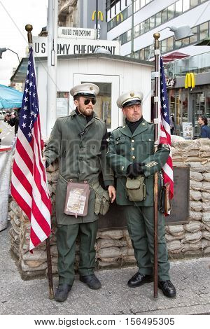 Berlin Germany - October 07 2016: Man dressed as an American soldier at Former Checkpoint Charlie the city center border crossing between West and East Berlin Germany Europe. With American flag