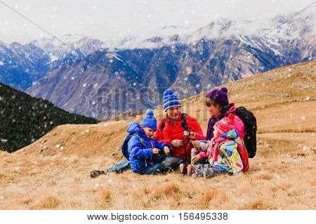family with two little kids travel in scenic winter mountains