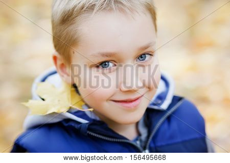 Cute smiling kid enjoying fall. Nature background.