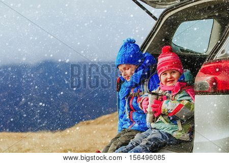 cute little boy and girl travel by car in winter mountains