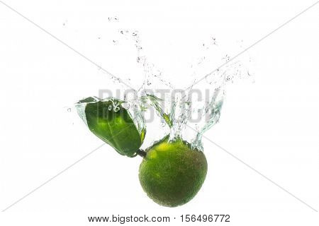 Green sweet tangerines splashes into the water isolated on white background