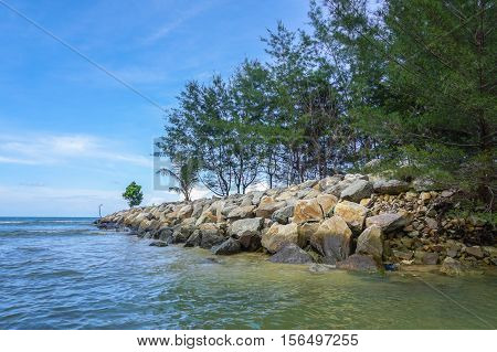 Stone embankment near sea shore with tropical tree in Labuan Pearl Of Borneo,Malaysia.Stone embankment to prevent the waves of the sea also ensure watertightness,support & stabilization.