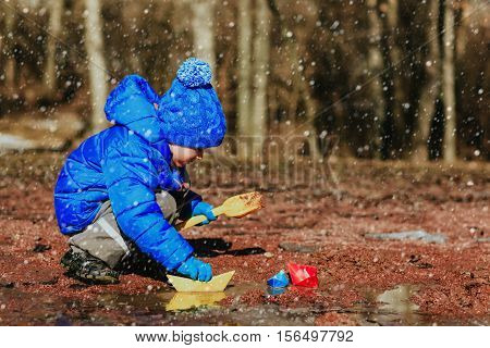 little boy plaing with paper boats in winter nature
