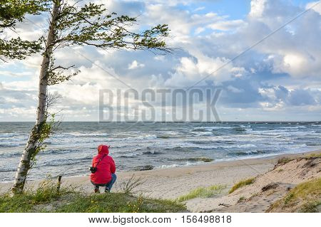 Girl sits on the beachfront and looks into the distance.