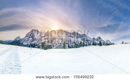 Winter sunshine over snowy mountains - Snowy panorama with the Austrian Alps the green coniferous forests and a valley covered by white snow.