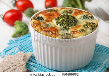 Healthy dietary breakfast. Broccoli casserole with eggs cheese in a white bowl fresh tomatoes crisp bread on the white wooden background