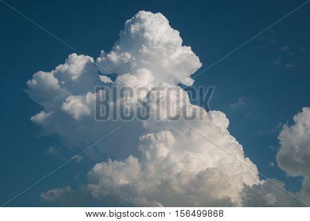 Big and fluffy cumulonimbus cloud in the blue sky