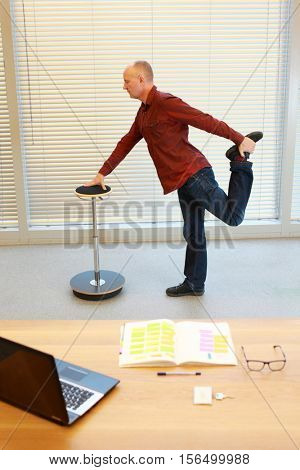leg exercise during office work - middle age  standing man stretching  on pneumatic stool in his office