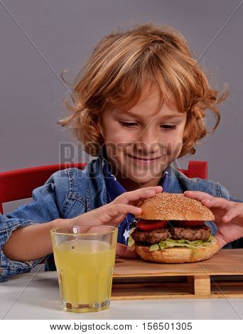Funny kid portrait eating burger.