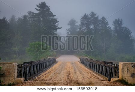 Dark forest over Corry Lake bridge.  Low cloud & darkened skies.  Surreal subdued light from summer storm over single lane, steel & timber bridge.