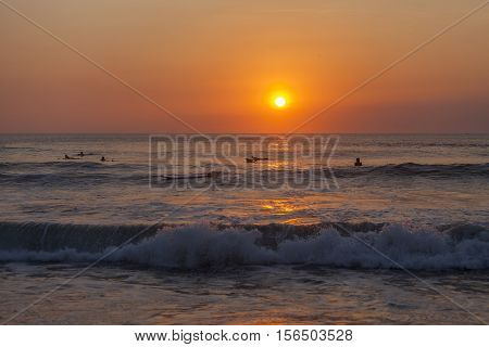 Silhouettes of surfers at the sunset at the Kuta beach, Bali, Indonesia
